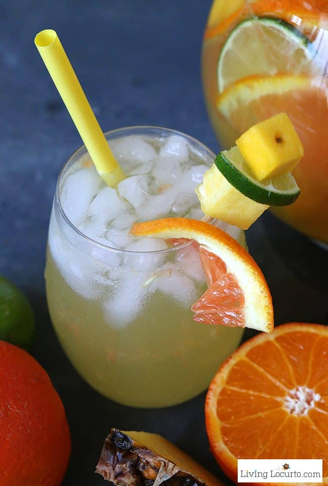 The best Tropical Pineapple Sangria recipe. A perfect drink for a luau party or sipping by the pool. A cocktail that makes you feel like you're at the beach! LivingLocurto.com