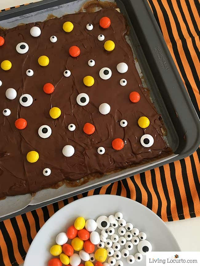 How to make Halloween Crack. An easy saltine cracker toffee recipe drizzled with chocolate, candy eyes and Halloween candy.