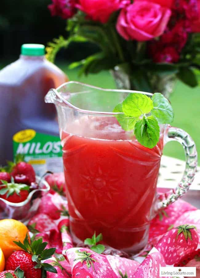 Strawberry cocktail by the pitcher with strawberries, mint, lemons and tea.