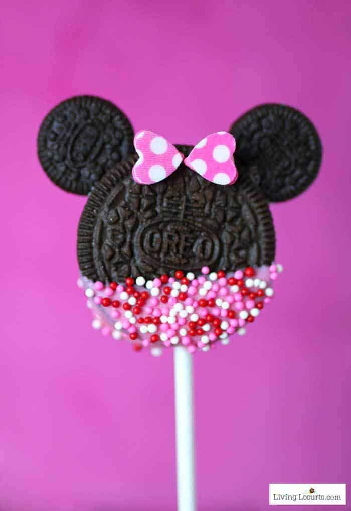 An Oreo cookie on a stick shaped and decorated to resemble Minnie Mouse
